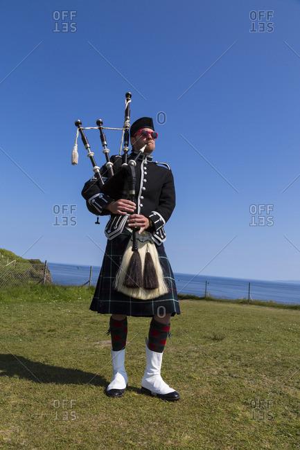 Isle of Skye, Scotland - June 6, 2016: Man playing bagpipes on the Isle of Skye