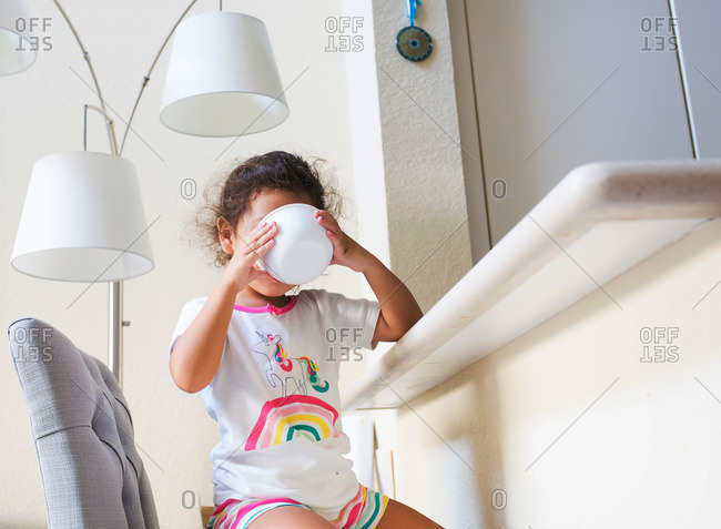 Girl drinking milk from a cereal bowl