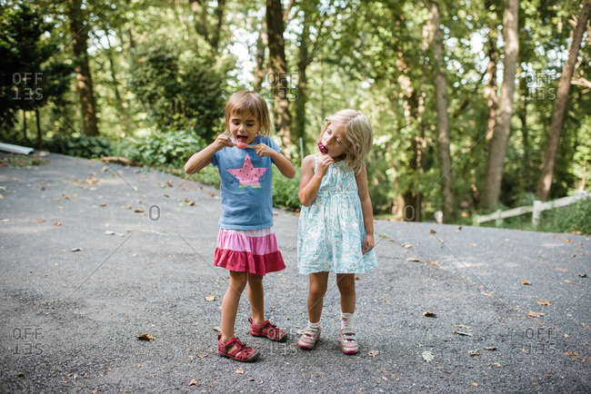 Two little girls eating popsicles