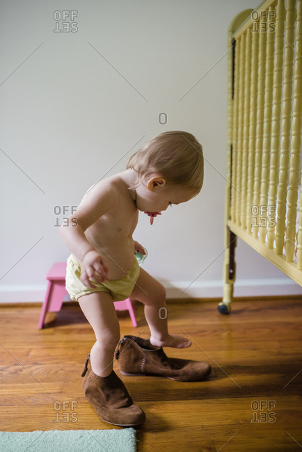 Baby stepping out of brown adult shoes