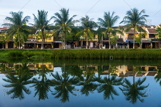 Hoi An, Vietnam - September 9, 2016: Palm trees reflected on river