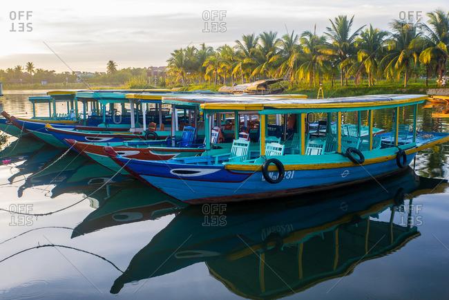 Hoi An, Vietnam - September 9, 2016: Tourists boats anchored on a river