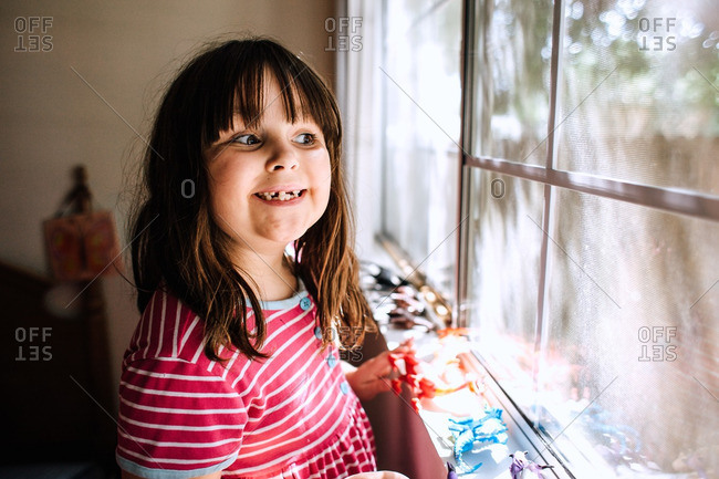 Girl by window with toys