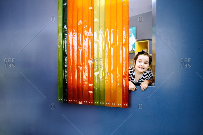 Smiling girl in window of play area