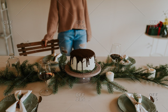 Woman standing near holiday table with cake and candlelight