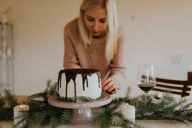 Woman decorating a cake with pine branches