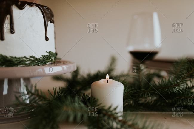 Votive candle among pine boughs next to holiday cake