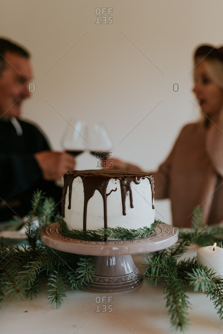 Man and woman toasting with wine at holiday cake