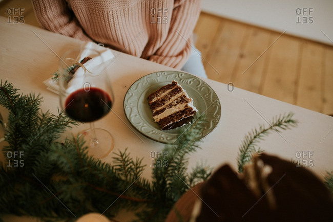 Elevated view of woman at holiday table with slice of cake and wine