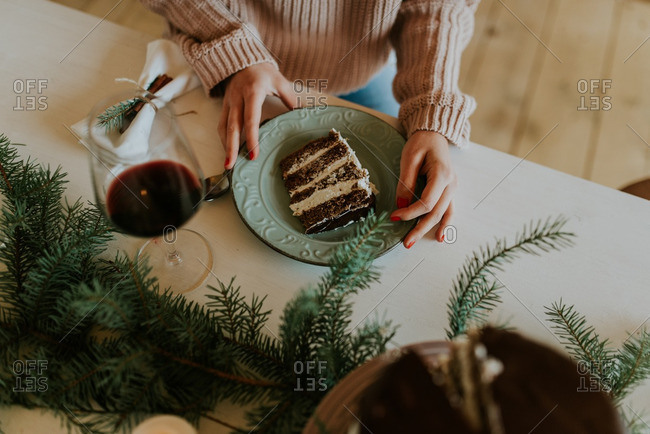 Woman enjoying slice of cake and wine at holiday table