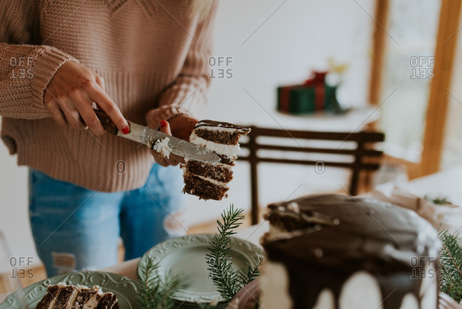 Woman serving a piece of cake at holiday table