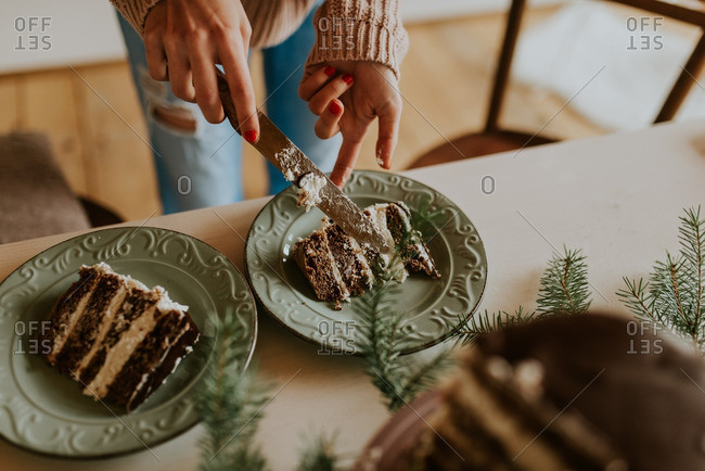 Woman serving slices of cake at holiday table