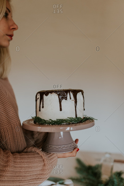 Woman carrying chocolate cake on cake stand