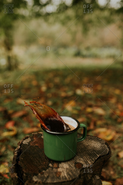 Mug of coffee splashing out of mug on log