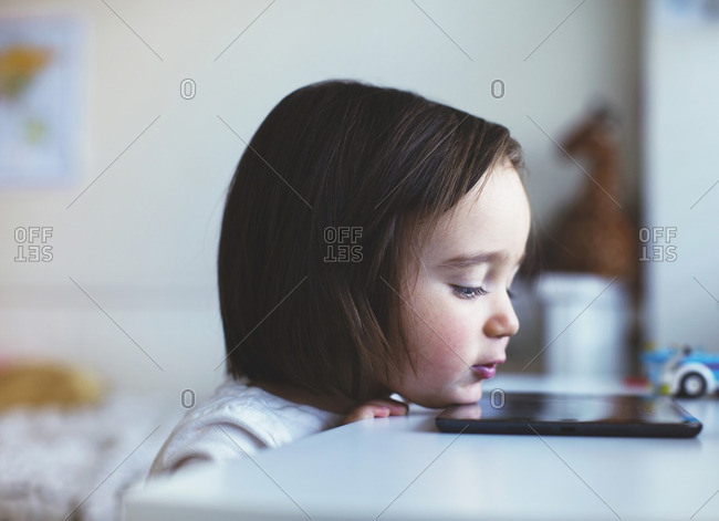 Girl watching tablet on a table