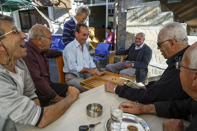Agros, Cyprus - May 7, 2015: Men playing backgammon at the main village square, Agros, Cyprus