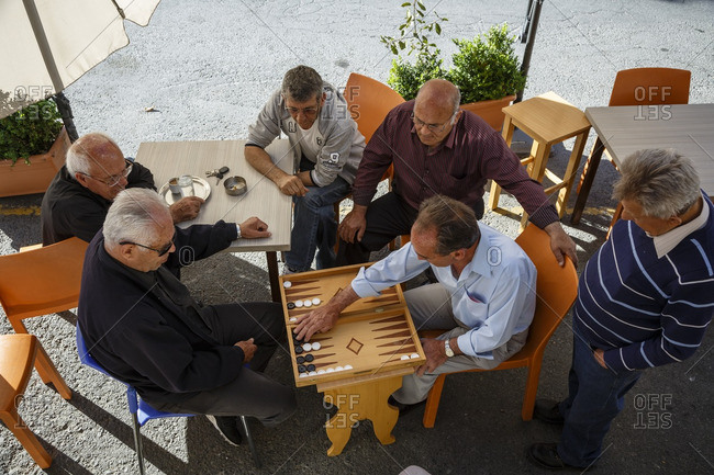 Agros, Cyprus - May 7, 2015: High angle view of men playing backgammon at the main village square, Agros, Cyprus
