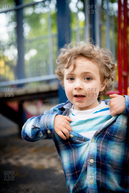 Portrait of a boy standing in front of playground equipment