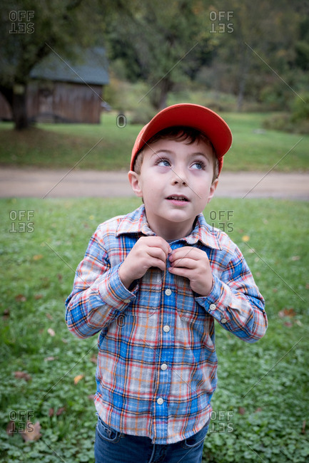 Portrait of a boy standing in yard buttoning his shirt