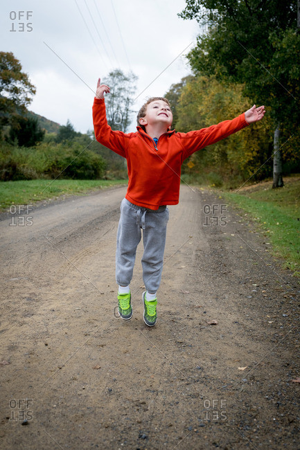 Boy leaping on gravel road