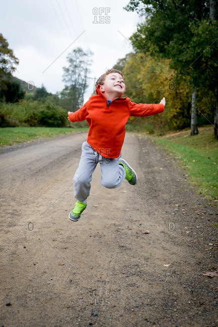 Boy jumping in the air above a gravel road in the country