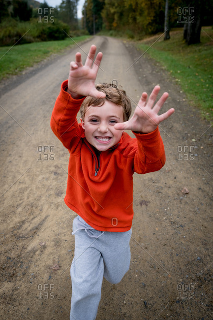 Boy with playful expression reaching his arms out