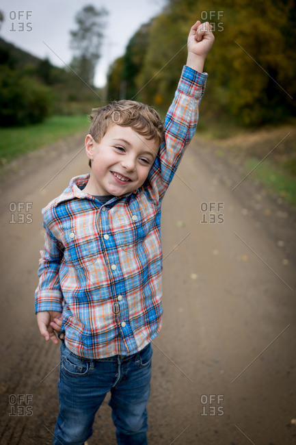 Smiling boy standing with his arm up