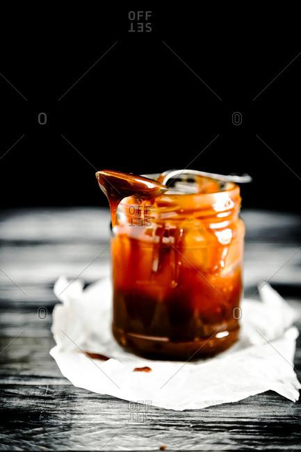Jar of homemade caramel sauce with spoon