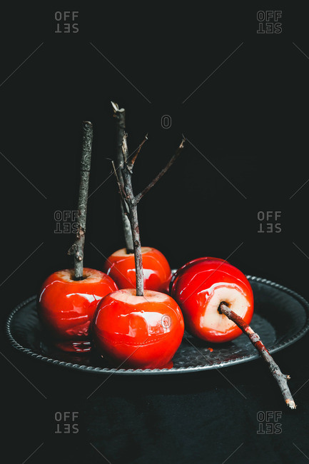 Four red candied apples on sticks served on a plate