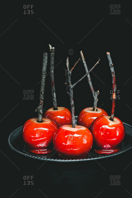 Five red candied apples on sticks served on a plate