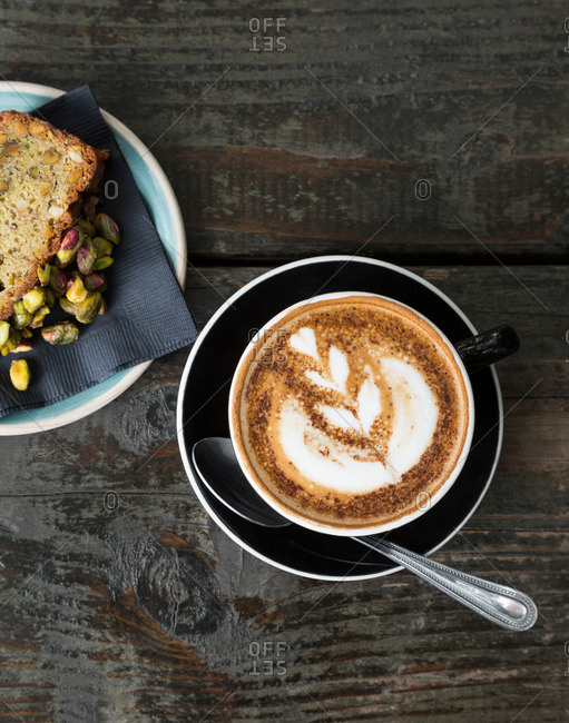Cappuccino and pistachio bread on rustic wood table