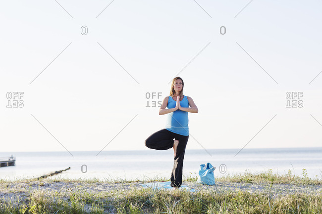 Pregnant woman doing tree pose at beach against clear sky