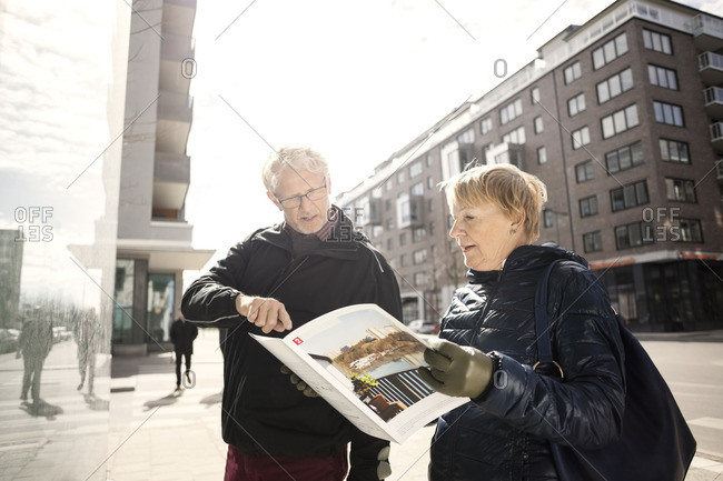 Senior couple reading catalog by building in city