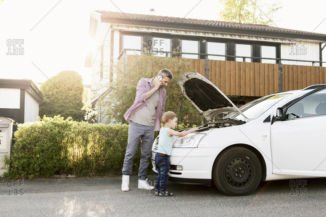 Father talking on phone standing with boy by broken down car on street