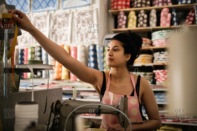 Woman reaching for tape measure while sewing textile in fabric shop