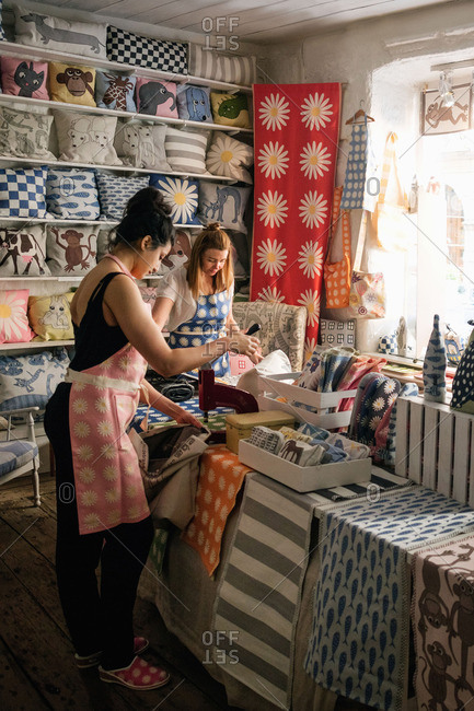 Female owners working on textile in shop
