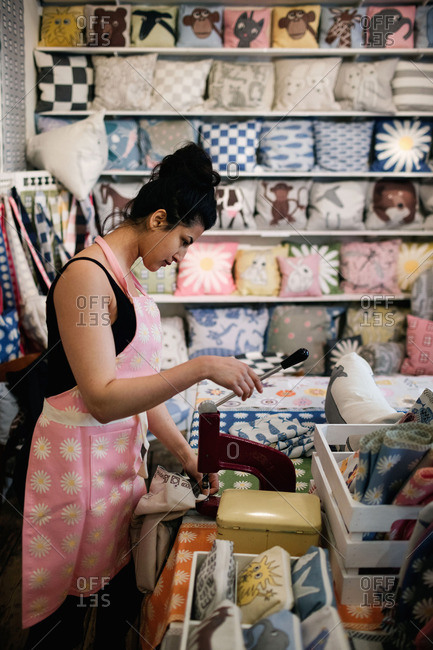 Side view of woman punching on textile while working in shop