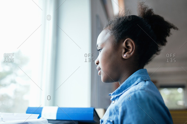 Close-up of thoughtful girl looking through window in classroom