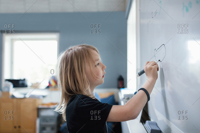 Side view of serious girl drawing on whiteboard in classroom