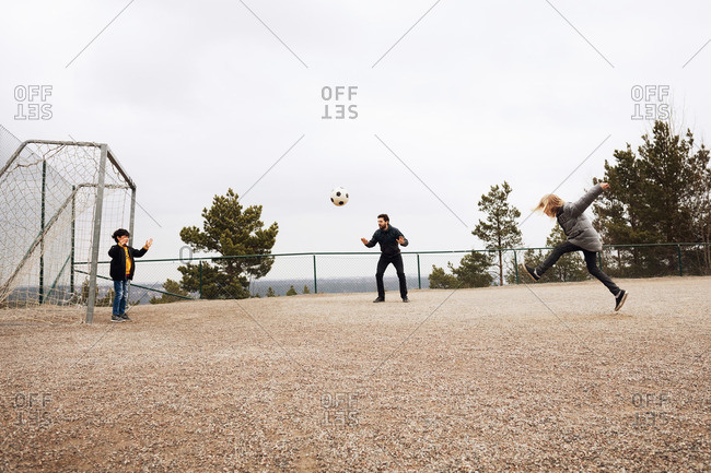 Teacher encouraging students while playing soccer on school playground