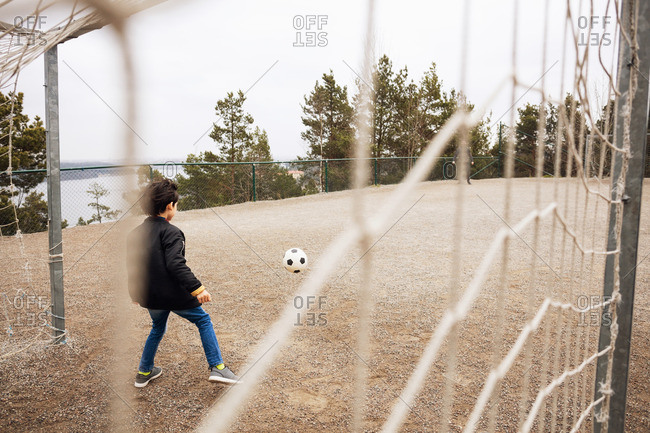 Rear view of boy standing on goal post at school playground