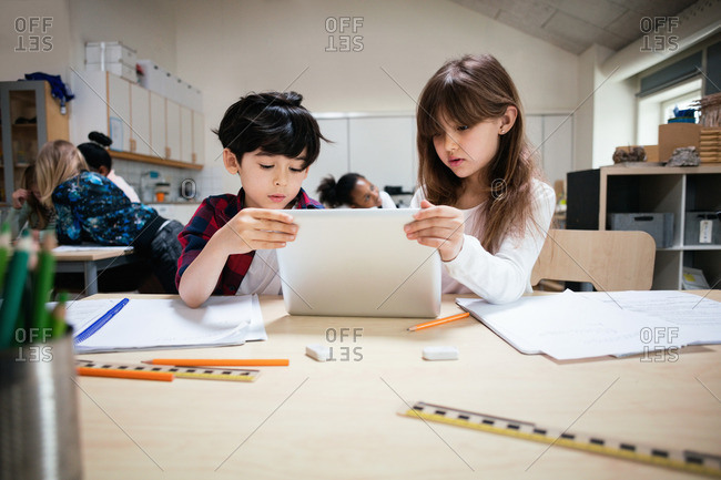 Concentrated students using digital tablet at desk in classroom