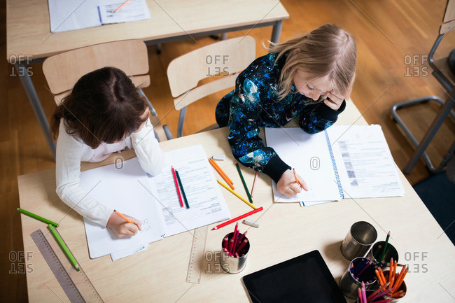 High angle view of schoolgirls studying at desk in school
