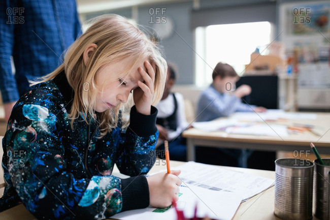 Concentrated girl studying at table in classroom