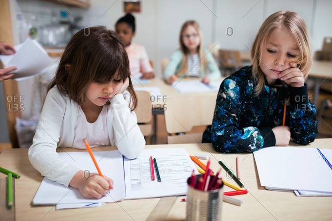 Students writing on paper at desk in classroom