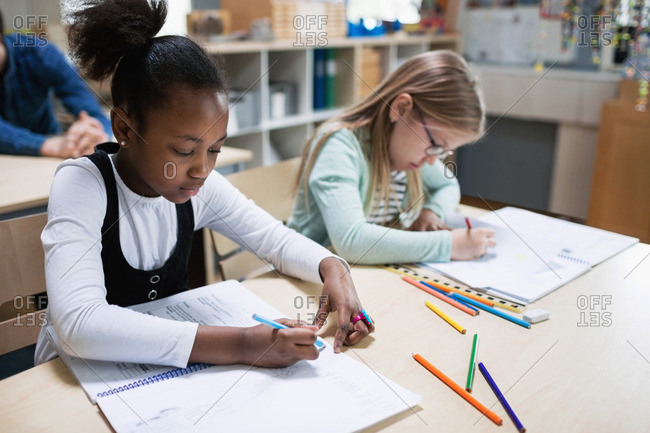 Schoolgirls studying at desk in classroom