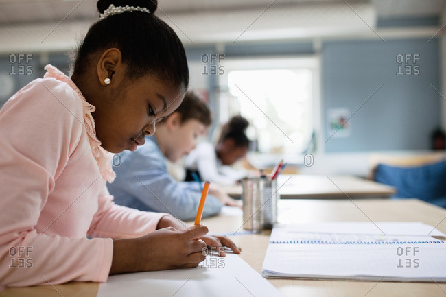 Concentrated students studying at desk in classroom
