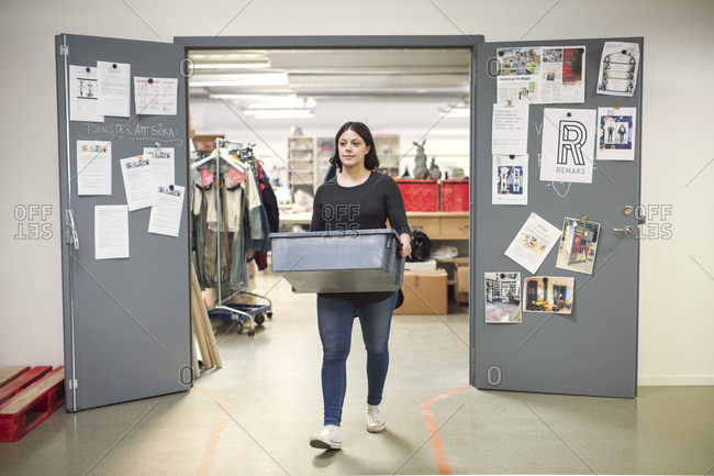 Woman carrying crate while walking out from doorway of workshop