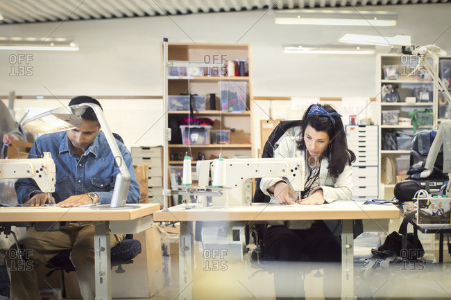 Serious man and woman sewing clothes at workshop