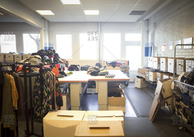 Various clothes and objects with boxes in brightly lit workshop